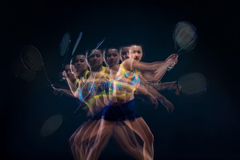 Stående av den härliga flickatennisspelaren med en racket på mörk bakgrund royaltyfri bild