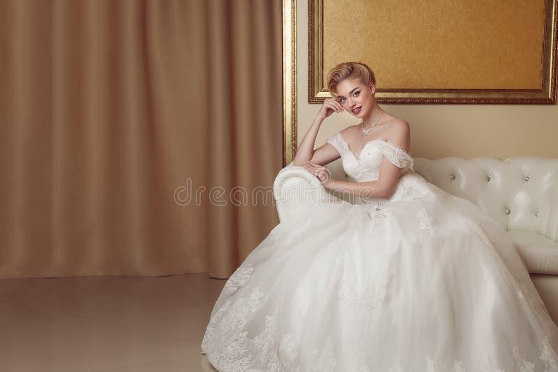Stående av den härliga gladlynta bruden i den vita klänningen Klassisk vagel royaltyfri bild