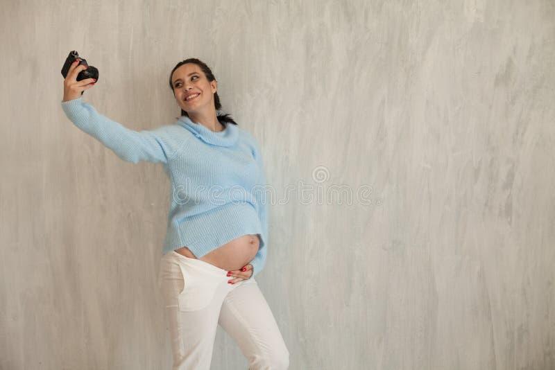 Stående av den härliga gravid kvinnafotografen i en fotofors royaltyfri bild