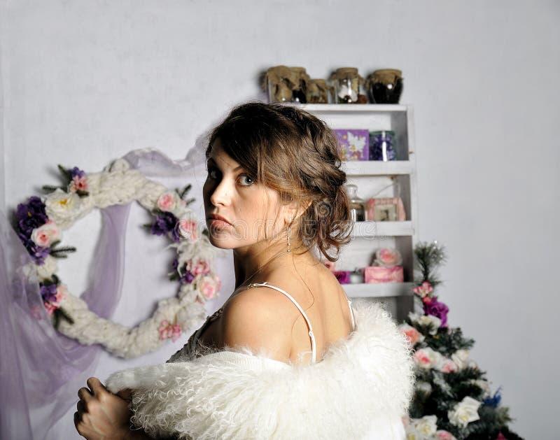 Stående av den härliga gravida unga kvinnan nära en julgran royaltyfri foto