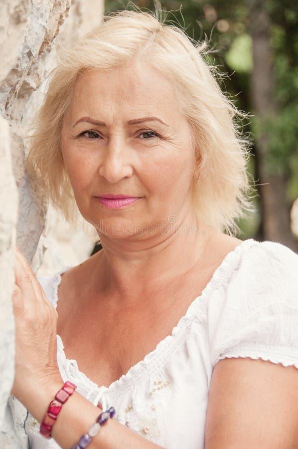 Stående av den härliga höga kvinnan med anseende för vitt hår vid w arkivbild