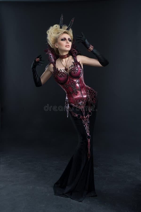 Stående av den härliga jäkelkvinnan i mörk sexig klänning arkivbild