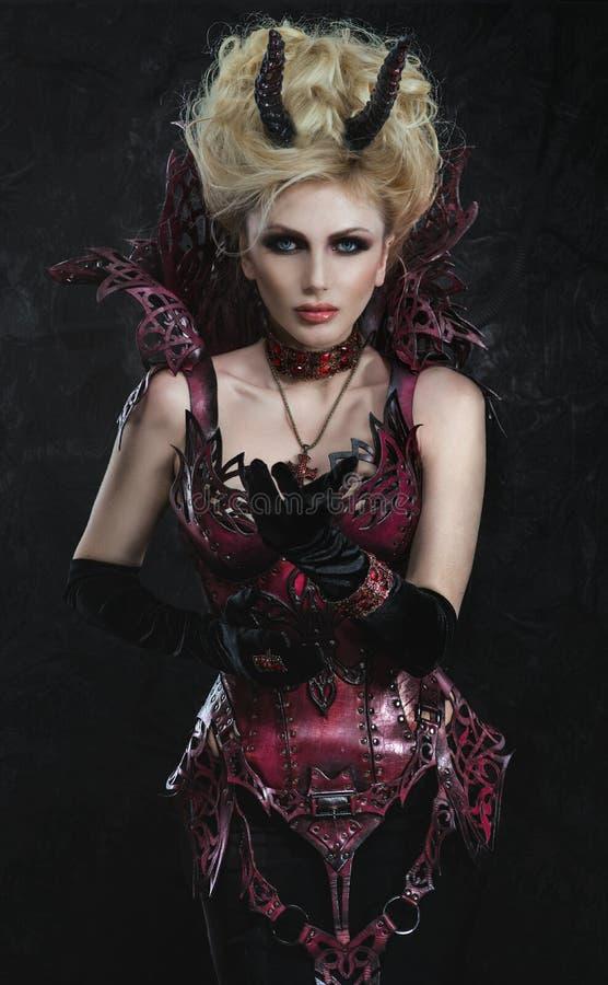 Stående av den härliga jäkelkvinnan i mörk sexig klänning arkivbilder