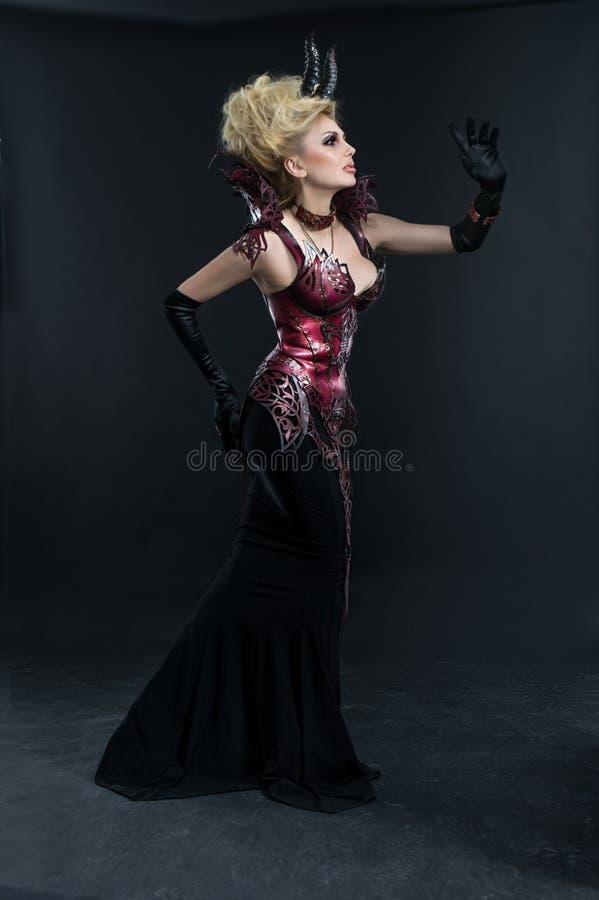 Stående av den härliga jäkelkvinnan i mörk sexig klänning royaltyfria bilder