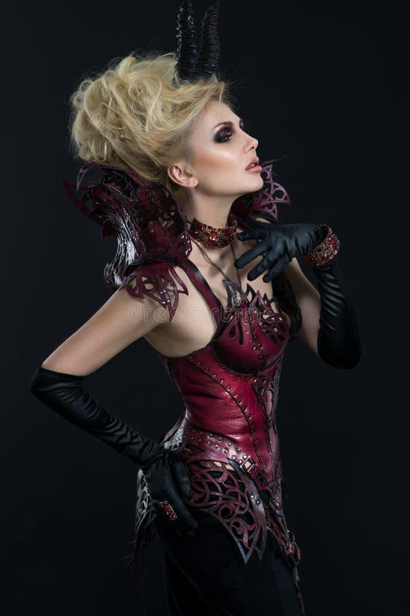 Stående av den härliga jäkelkvinnan i mörk sexig klänning arkivfoton