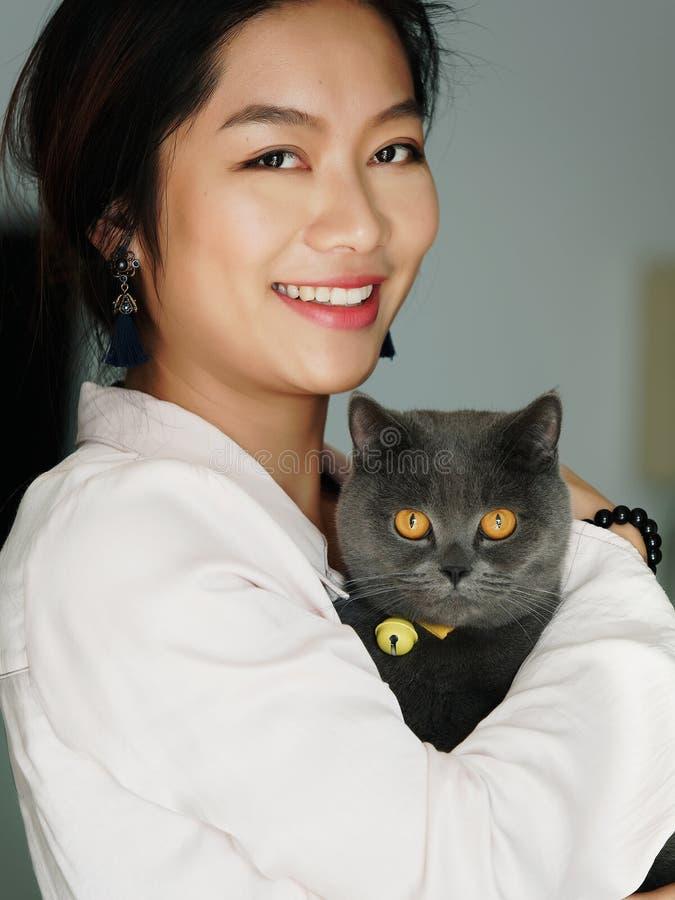 Stående av den härliga kinesiska ung flickakramen hennes gulliga brittiska Shorthair katt som har fantastiska orange ögon hemma i royaltyfri bild