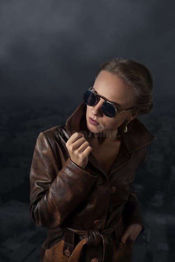 Stående av den härliga kvinnan i brunt läderlag och solglasögon royaltyfri bild