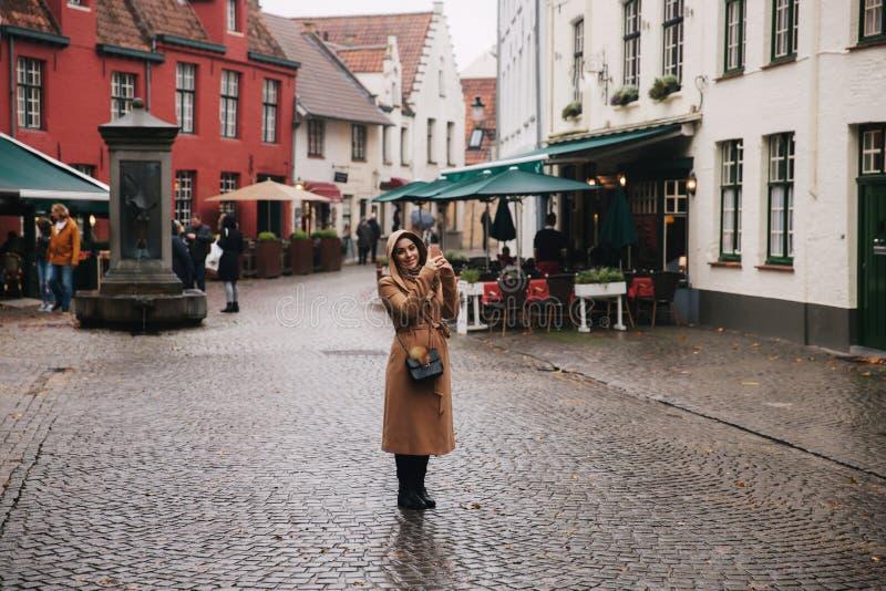 Stående av den härliga kvinnan i det bruna laget som gör ett foto i Bealgium, Brugge Manligt pålagt en huv arkivfoton