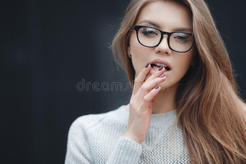 Stående av den härliga kvinnan i exponeringsglas på grå bakgrund arkivbild