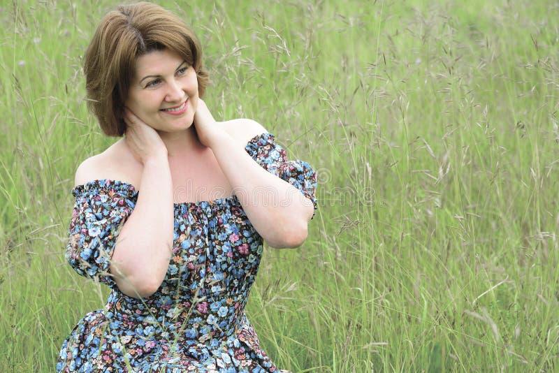 Stående av den härliga kvinnan i gräset på en sommardag fotografering för bildbyråer