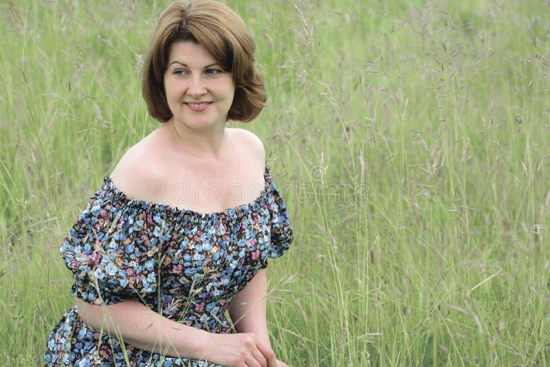 Stående av den härliga kvinnan i gräset på en sommardag arkivfoton