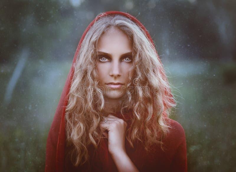 Stående av den härliga kvinnan i röd huv royaltyfri fotografi