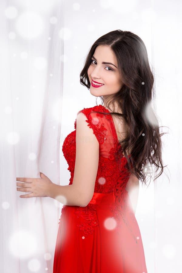 Stående av den härliga kvinnan i röd klänning över vit arkivfoton