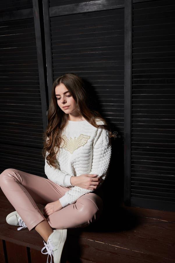 Stående av den härliga kvinnan i rosa färgflåsanden och den vita tröjan royaltyfri fotografi
