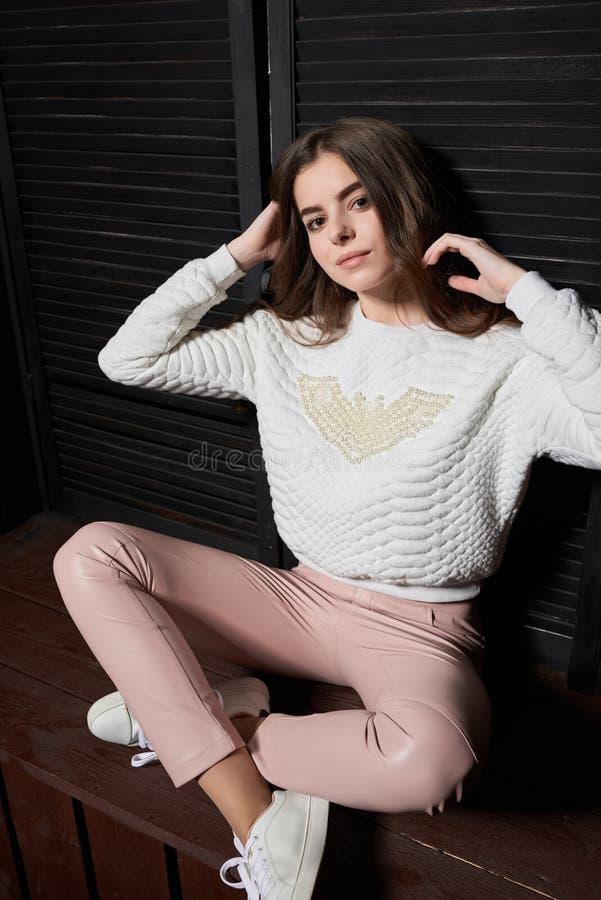 Stående av den härliga kvinnan i rosa färgflåsanden och den vita tröjan royaltyfri foto