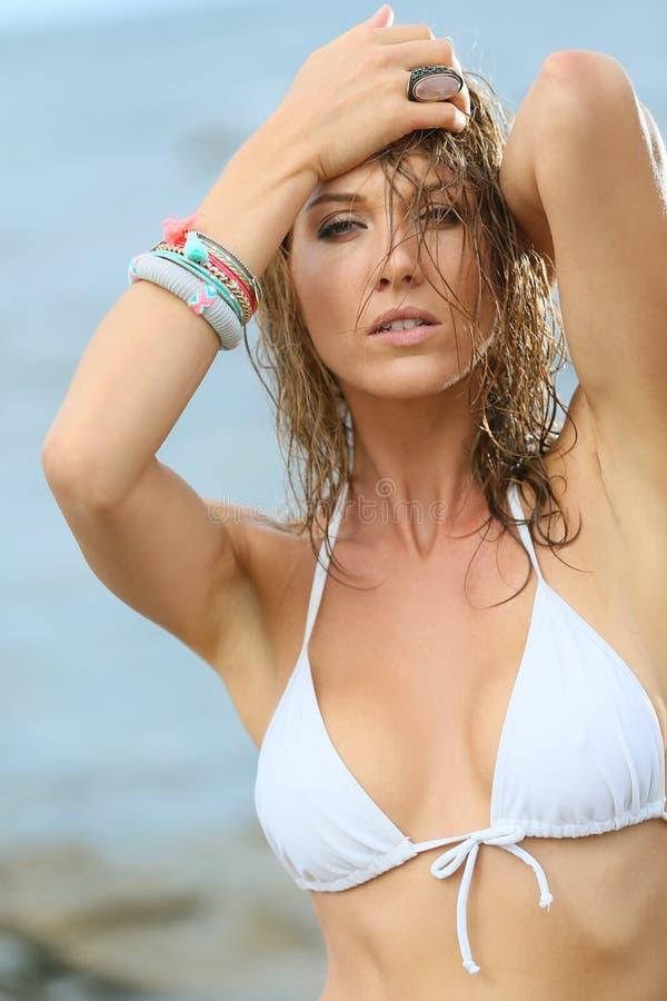 Stående av den härliga kvinnan med den våta hår och vitbikinin royaltyfria foton