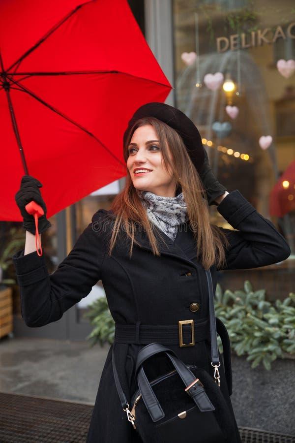 Stående av den härliga kvinnan med det röda paraplyet framme av ett kafé i staden arkivbild