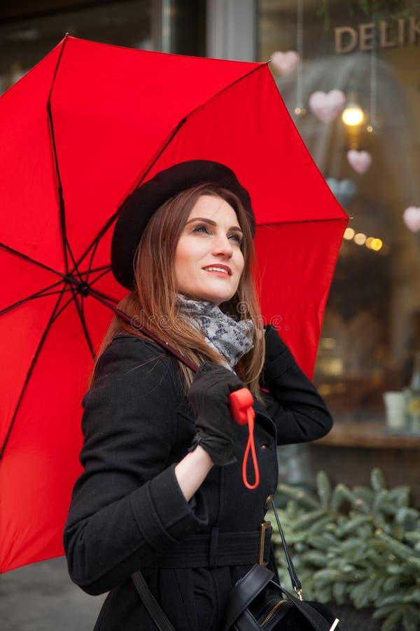 Stående av den härliga kvinnan med det röda paraplyet framme av ett kafé i staden royaltyfri foto