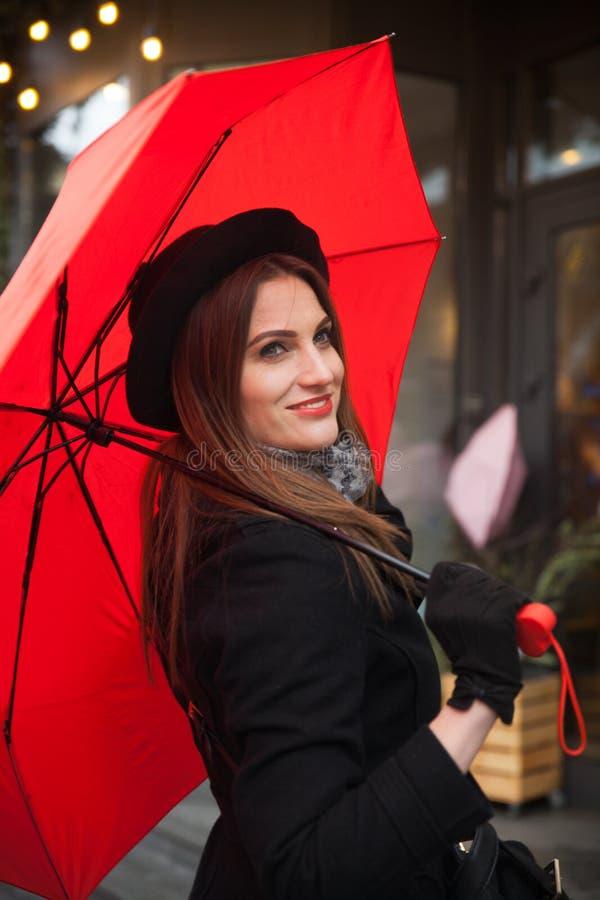 Stående av den härliga kvinnan med det röda paraplyet framme av ett kafé i staden arkivfoto