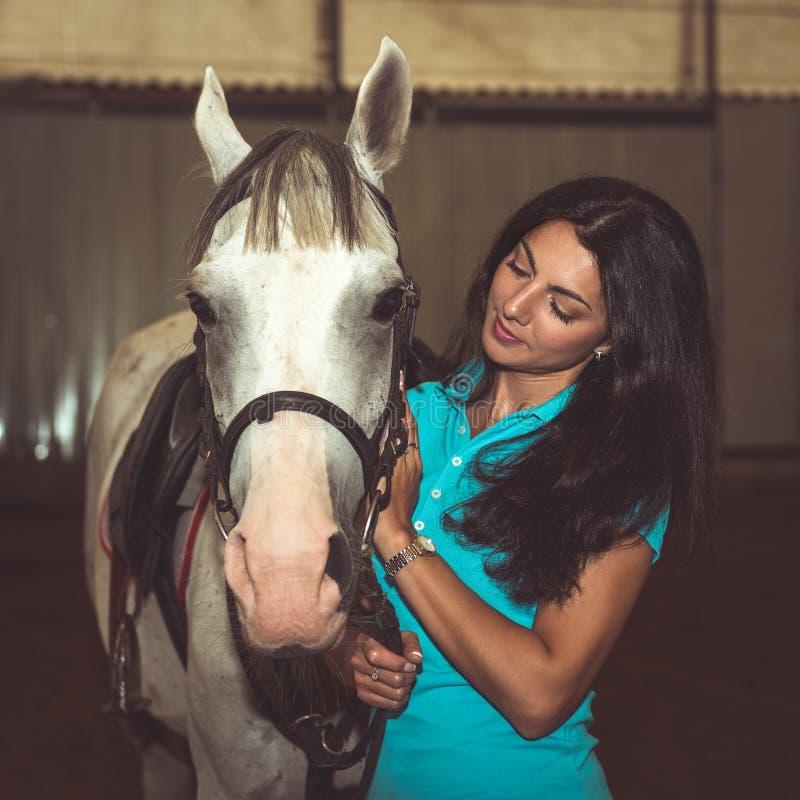 Stående av den härliga kvinnan med en häst royaltyfri foto
