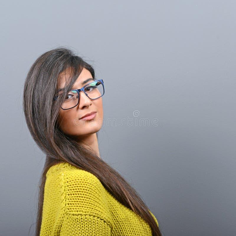 Stående av den härliga kvinnan med exponeringsglas som poserar mot grå bakgrund royaltyfri foto