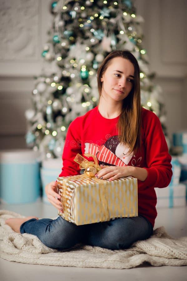 Stående av den härliga kvinnan med gåvasammanträde vid julgranen hemma arkivfoto