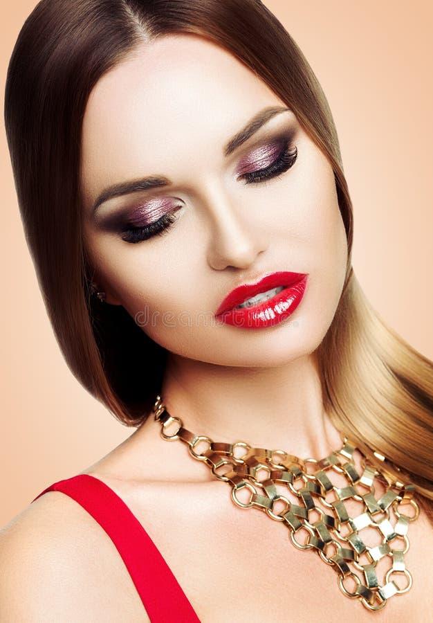 Stående av den härliga kvinnan med ljus aftonmakeup för skönhet Flickan annonserar ögonskugga Hårraksträcka som är slät royaltyfria foton