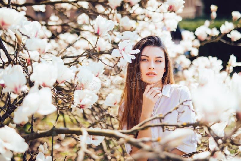 Stående av den härliga kvinnan med magnoliablommor Fjädra den tid… ron lämnar, naturlig bakgrund royaltyfri bild
