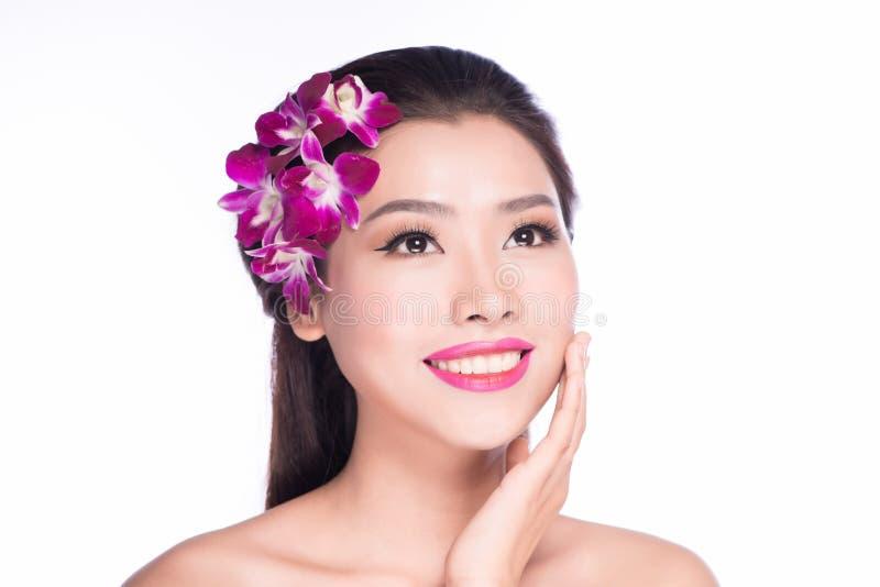 Stående av den härliga kvinnan med orkidéblomman i hennes hår Beautiful modellerar kvinnan vänder mot perfekt hud applicera glans royaltyfri foto