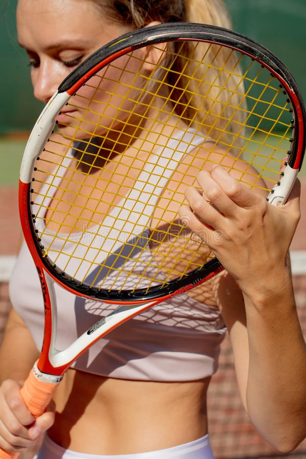 Stående av den härliga kvinnan med den utomhus- tennisraket Sommarsportrekreation royaltyfria foton