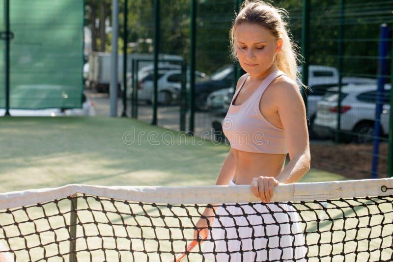 Stående av den härliga kvinnan med den utomhus- tennisraket Sommarsportrekreation royaltyfri fotografi