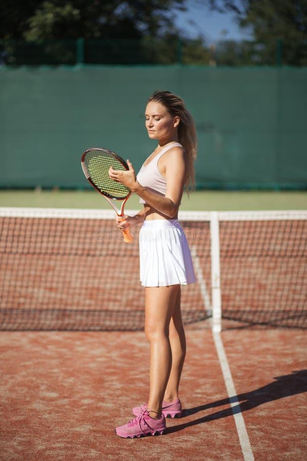 Stående av den härliga kvinnan med den utomhus- tennisraket Sommarsportrekreation royaltyfri bild