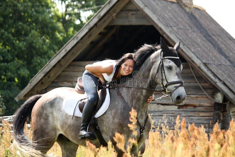 Stående av den härliga kvinnan på häst nära ladugården arkivfoton
