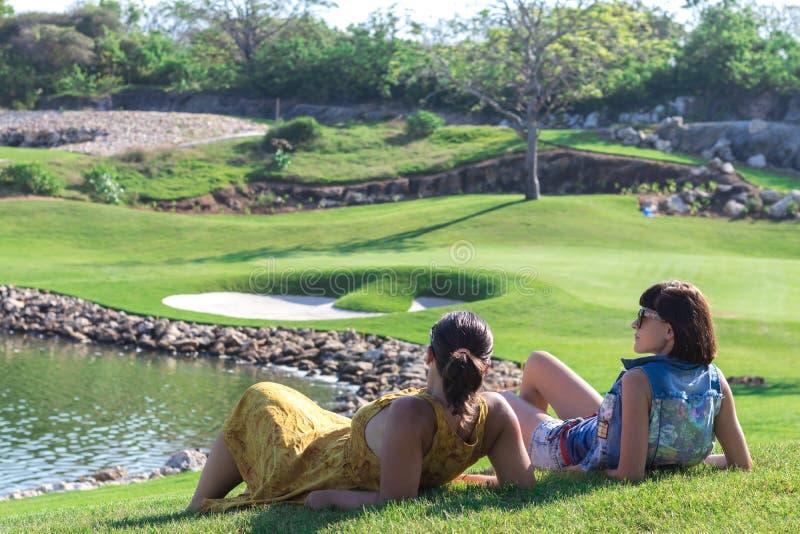Stående av den härliga kvinnan som kopplar av under att spela golf på en grön bakgrund för fält utomhus Tropisk Bali ö arkivbild