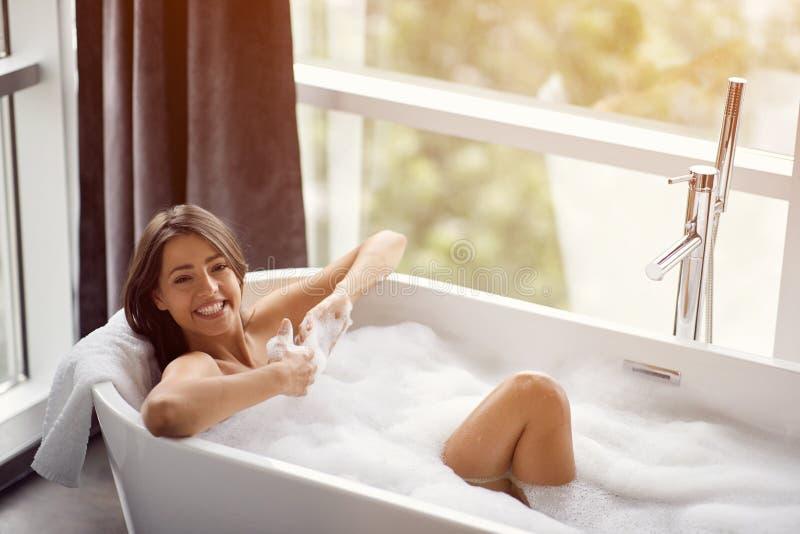 Stående av den härliga kvinnan som kopplar av i bad med skum fotografering för bildbyråer