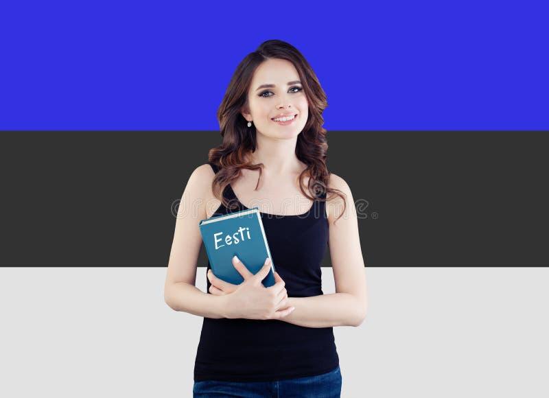 Stående av den härliga kvinnastudenten med boken mot den Estland flaggabakgrunden Lär det estonian språkbegreppet royaltyfri foto