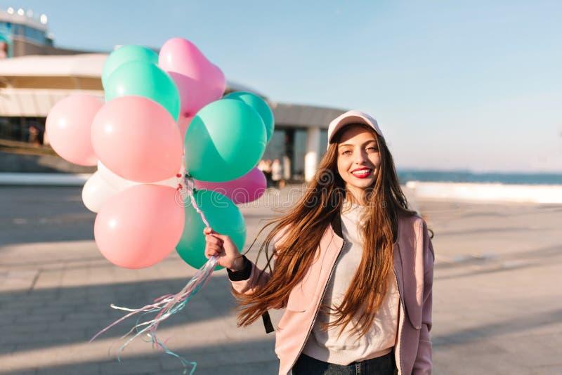 Stående av den härliga långhåriga brunettflickan som poserar på havspir medan vind som vinkar hennes hår f?rtjusande kvinnabarn royaltyfri foto