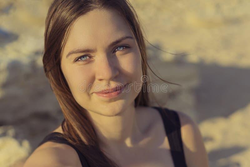 Stående av den härliga le flickan som ser kameran med glat och charmigt leende på en bakgrund av en sandig strand på solnedgången royaltyfri fotografi
