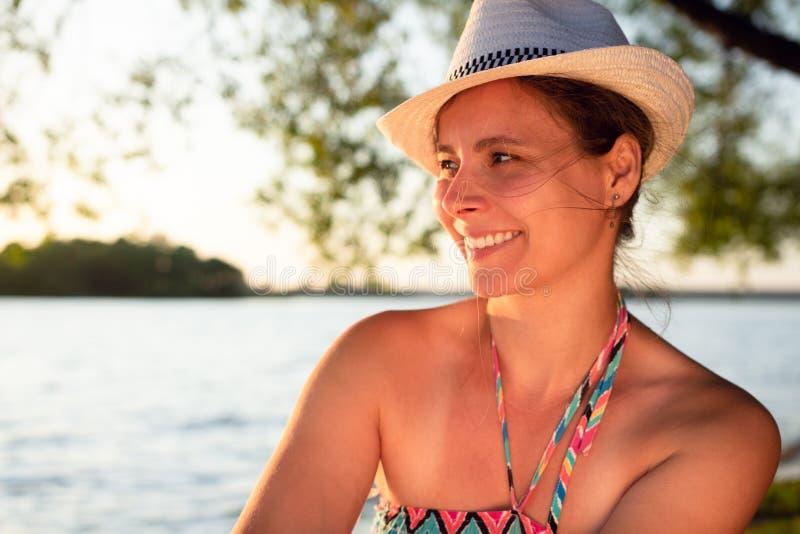 Stående av den härliga le kvinnan i hatt på lakeside på solnedgången royaltyfri fotografi