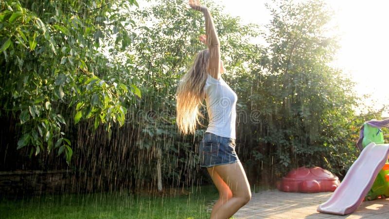 Stående av den härliga le kvinnan i våt kläder som tycker om varmt regn på husträdgårdträdgården på solnedgången leka f?r flicka fotografering för bildbyråer