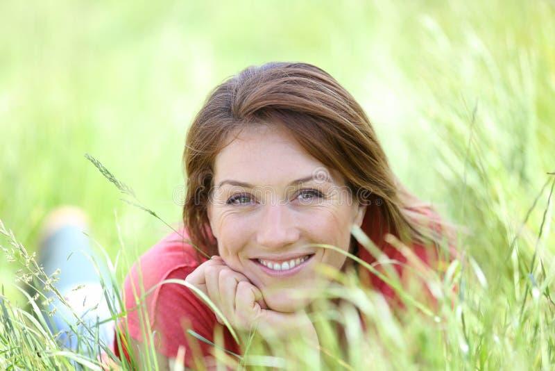 Stående av den härliga le kvinnan som ligger i gräs fotografering för bildbyråer