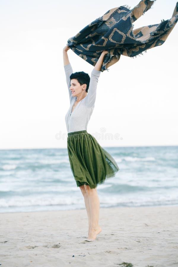 Stående av den härliga le skratta Caucasian brunettkvinnan med kort hår i den gråa skjortan, för ballerinakjoltyll för grön oliv  royaltyfri fotografi