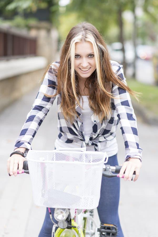 Stående av den härliga le unga kvinnan med cykeln i gatan arkivfoton