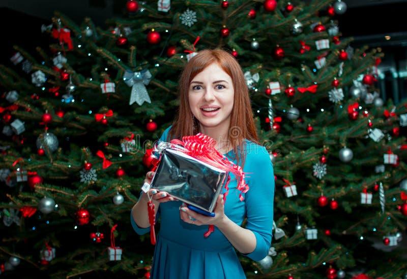Stående av den härliga le unga kvinnan och att stå nära julgranen som rymmer gåvan arkivfoton