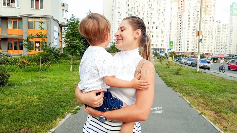 Stående av den härliga le unga modern som rymmer hennes litet barnson och går på gatan arkivbild