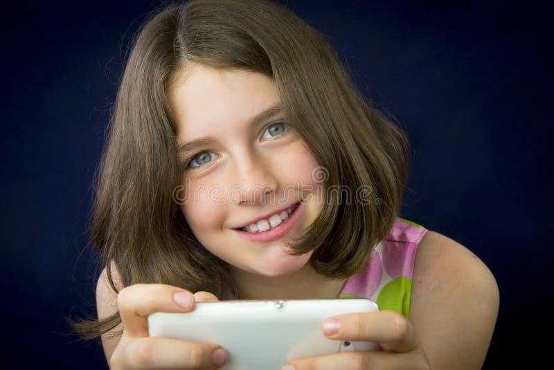 Stående av den härliga lilla flickan med mobiltelefonen royaltyfria bilder