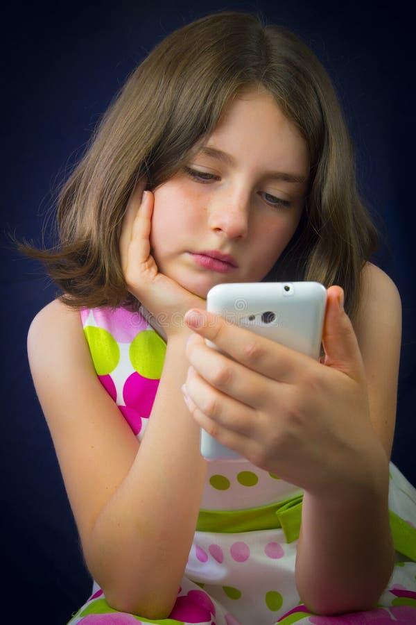 Stående av den härliga lilla flickan med mobiltelefonen royaltyfri bild