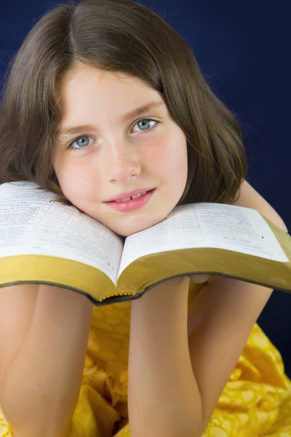Stående av den härliga lilla flickan som rymmer den heliga bibeln royaltyfria foton
