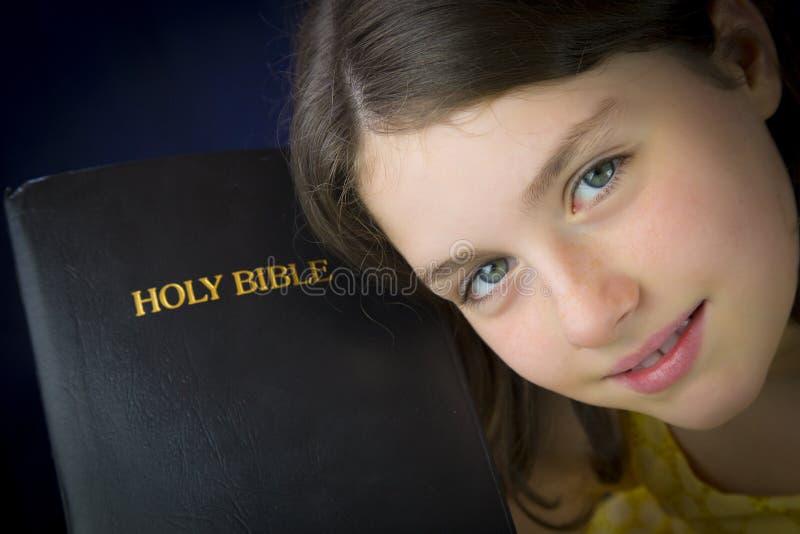 Stående av den härliga lilla flickan som rymmer den heliga bibeln arkivfoton