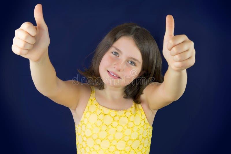 Stående av den härliga lilla flickan som visar det ok tecknet royaltyfria bilder